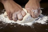 Woman's Hands Kneading Dough On Wooden Table