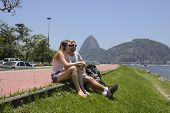 Couple of tourists sitting on the edge of Guanabara Bay with the Sugar Loaf in the background.
