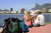 Group of backpackers tourists friends sitting on the edge of Guanabara bay watching the Christ the R