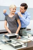 Male puts necklace on his girlfriend at jeweler's shop. Concept of wealth and luxurious life
