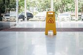 image of slip hazard  - wet floor sign on the floor near an outdoor parking - JPG