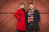 Young Mixed Race Couple Portrait in Winter Clothing Against Barn Door.