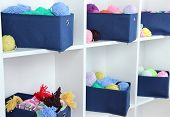 Blue textile boxes with yarn in white shelves