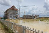 It Shows Construction Cranes And Unfinished House On The Skyline