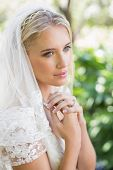 Smiling bride in a veil holding her hands to her chest in the countryside