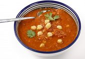 Spicy tomato and chickpea soup in a traditional Tunisian bowl with a spoon, garnished with parsley.