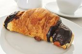 a chocolate croissant in a plate on a set table with a cup of coffee in the background