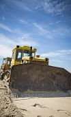picture of bulldozers  - Bulldozer at work on blue sky background - JPG