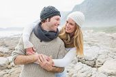 Happy romantic young couple standing together on a rocky landscape