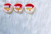 Christmas cookies with santa face on white fur background with copy space