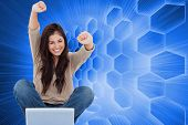 Composite image of a woman celebrating in front of her laptop as she smiles looking forward.