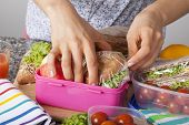 stock photo of lunch box  - A closeup of hands packing snacks into a pink lunch box