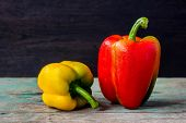 red and yellow sweet peppers on wood background