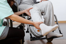 foto of physiotherapist  - Young physiotherapist exercising with elder disabled person - JPG