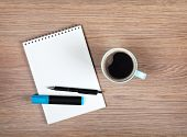 Blank notepad and coffee cup on office wooden table