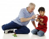 A preschooler carefully studying the toy dinosaur as he grandpa points out features.  On a white bac