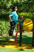 stock photo of swinger  - Mature woman at the outdoor gym circuit working out on a air swinger machine in the green sunny park