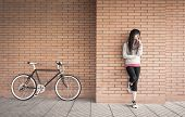 Sportive woman with fixie bike over a brick wall