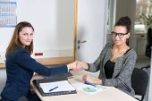 Two Women Doing A Handshake During A Meeting