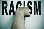 a man punching the word racism, depicting the concept of the fight against racism