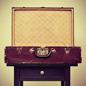 an open old suitcase on a table, with a retro effect