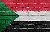 Flag of Sudan painted onto a grunge brick wall