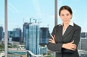 Young business woman in her office overseeing the city skyline.