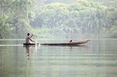 Man In Traditional Boat On Tropical River Volta In Ghana, West Africa.