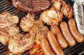 Various meats like chicken, sausage, steak and corn wrapped in aluminum foil on a barbecue grill