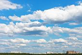 Cityscape With White Fluffy Clouds In Blue Sky