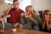 foto of crystal meth  - Parents Sit On Sofa With Children Taking Drugs And Drinking - JPG