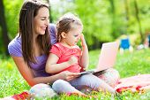 Mother with child using laptop outdoors