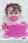 Baby girl eating first birthday cake with pink frosting and bow in her hair