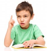 Cute little boy is reading a book while pointing up using his index finger, isolated over white