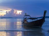 Colorful sunset on the beach with silhouette of longtail boat. Krabi, Thailand.