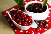 Fresh and dry cranberry in bowls on wooden table close-up