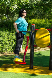 picture of swingers  - Mature woman at the outdoor gym circuit working out on a air swinger machine in the green sunny park  - JPG