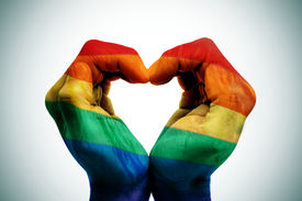 stock photo of bisexual  - man hands patterned as the rainbow flag forming a heart - JPG