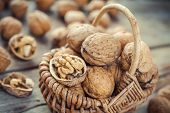 Walnuts In Wicker Basket On Old Wooden Rustic Table. Selective Focus.