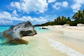 Beautiful tropical beach with white sand, turquoise ocean water and blue sky at Virgin Gorda, British Virgin Islands in Caribbean