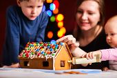 Family decorating gingerbread house on Christmas eve. Focus on house