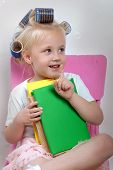 The Little Girl Sits On A Chair Whith Hair Curlers On Her Head