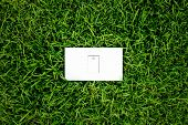Energy concept light switch in fresh spring green grass
