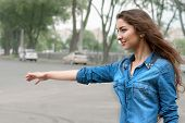 Young Woman Hitch-hiking In Sity