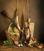 Classic still life with dead pheasant and hare combined with autumn fruits and hunting rifle