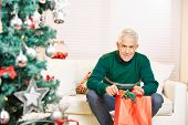 Senior man sitting with gift at christmas eve at home