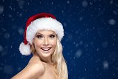 Beautiful woman in Christmas cap,blue snowy background