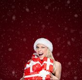 Pretty woman in Christmas cap holds a set of presents, snowy background