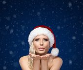 Attractive woman in Christmas cap blows kiss, snowflakes background