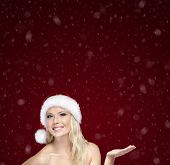 Attractive woman in Christmas cap gestures palm up, on snowfall background